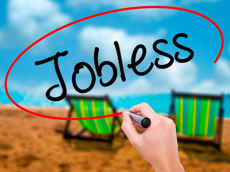 Man Hand writing  Jobless  with black marker on visual screen. Isolated on sunbed on the beach. Business, technology, internet concept. Stock Photo