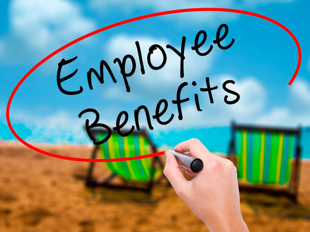 Man Hand writing Employee Benefits with black marker on visual screen. Isolated on sunbed on the beach. Business, technology, internet concept. Stock Photo