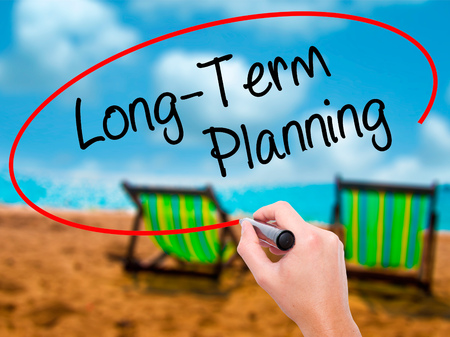 ltc: Man Hand writing  Long-Term Planning with black marker on visual screen. Isolated on sunbed on the beach. Business, technology, internet concept. Stock Photo
