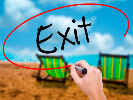 Man Hand writing Exit with black marker on visual screen. Isolated on sunbed on the beach. Business, technology, internet concept. Stock Photo