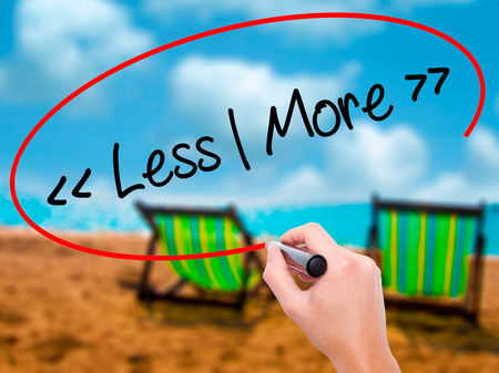 Man Hand writing Less - More with black marker on visual screen. Isolated on sunbed on the beach. Business, technology, internet concept. Stock Photo