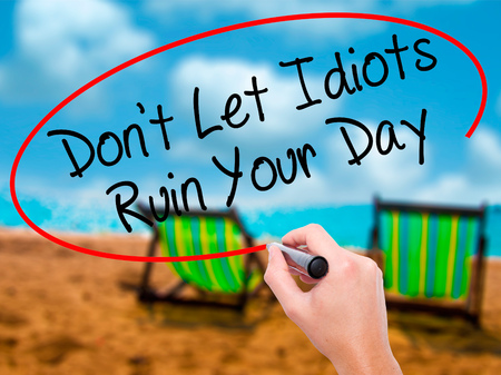 stupidity: Man Hand writing Dont Let Idiots Ruin Your Day with black marker on visual screen. Isolated on sunbed on the beach. Business, technology, internet concept. Stock Photo Stock Photo
