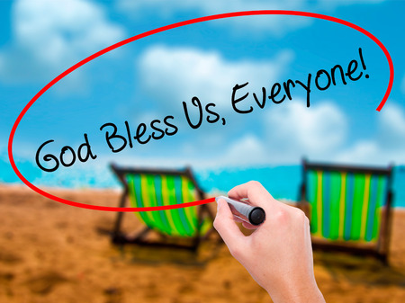 preachment: Man Hand writing God Bless Us, Everyone! with black marker on visual screen. Isolated on sunbed on the beach. Business, technology, internet concept. Stock Photo