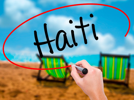 Man Hand writing Haiti with black marker on visual screen. Isolated on sunbed on the beach. Business, technology, internet concept. Stock Photo