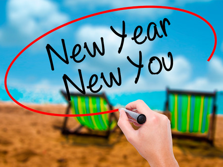 Man Hand writing New Year New You with black marker on visual screen. Isolated on city. Business, technology, internet concept. Stock Photo