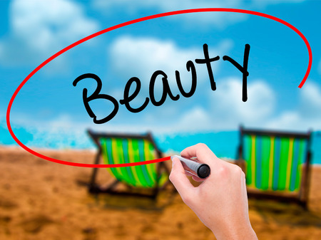 Man Hand writing Beauty  with black marker on visual screen. Isolated on sunbed on the beach. Business, technology, internet concept. Stock Photo Stock Photo