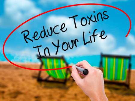 toxins: Man Hand writing Reduce Toxins In Your Life with black marker on visual screen. Isolated on sunbed on the beach. Business, technology, internet concept. Stock Photo