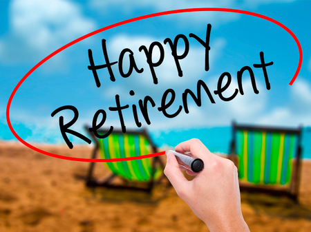 Man Hand writing Happy Retirement  with black marker on visual screen. Isolated on sunbed on the beach. Business, technology, internet concept. Stock Photo