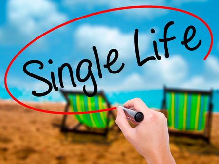 Man Hand writing Single Life with black marker on visual screen. Isolated on sunbed on the beach. Business, technology, internet concept. Stock Photo