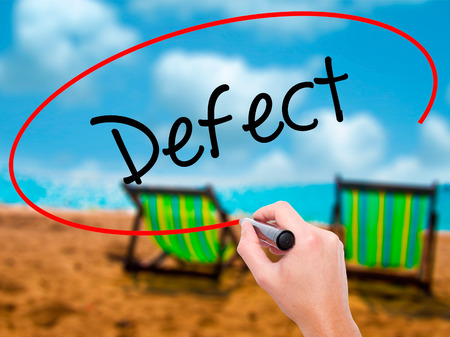 Man Hand writing Defect with black marker on visual screen. Isolated on sunbed on the beach. Business, technology, internet concept. Stock Photo