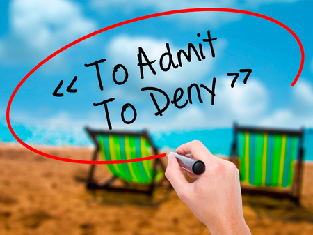 contradict: Man Hand writing To Admit - To Deny with black marker on visual screen. Isolated on sunbed on the beach. Business, technology, internet concept. Stock Photo