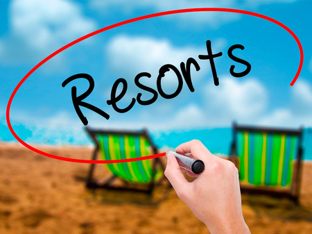 Man Hand writing Resorts  with black marker on visual screen. Isolated on sunbed on the beach. Business, technology, internet concept. Stock Photo