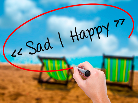 Man Hand writing Sad - Happy with black marker on visual screen. Isolated on sunbed on the beach. Business, technology, internet concept. Stock Photo
