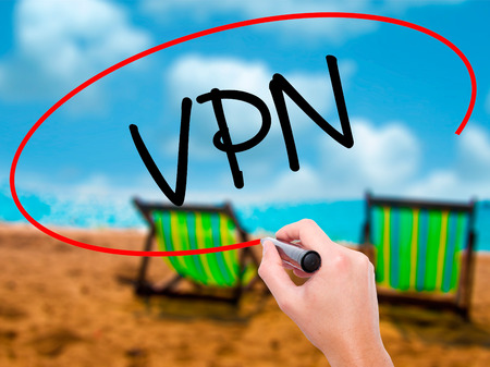 Man Hand writing VPN (Virtual Private Network) with black marker on visual screen. Isolated on sunbed on the beach. Business, technology, internet concept. Stock Photo