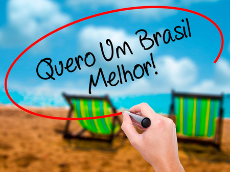 Man Hand writing Quero Um Brasil Melhor!  ( I want a Better Brazil in Portuguese)with black marker on visual screen. Isolated on sunbed on the beach. Business, technology, internet concept. Stock Photo