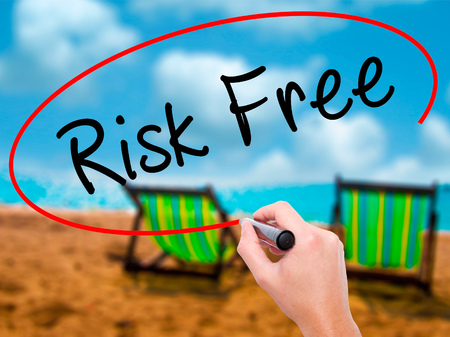 Man Hand writing Risk Free with black marker on visual screen. Isolated on sunbed on the beach. Business, technology, internet concept. Stock Image