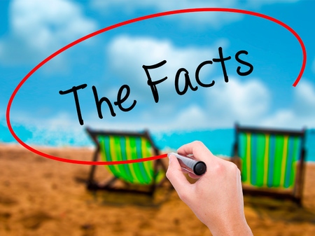 Man Hand writing The Facts  with black marker on visual screen. Isolated on sunbed on the beach. Business, technology, internet concept. Stock Photo