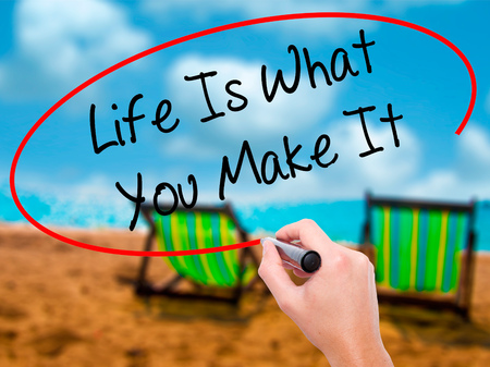 leadership potential: Man Hand writing Life Is What You Make It with black marker on visual screen. Isolated on sunbed on the beach. Business, technology, internet concept. Stock Photo