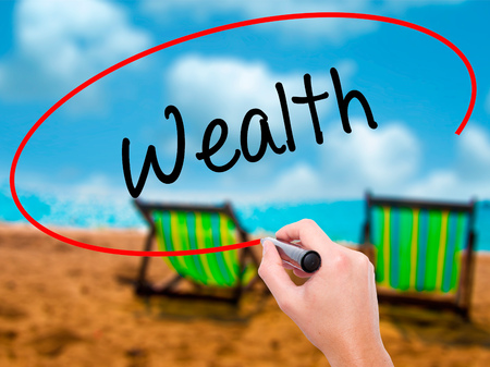 Man Hand writing Wealth with black marker on visual screen. Isolated on sunbed on the beach. Business, technology, internet concept. Stock Photo