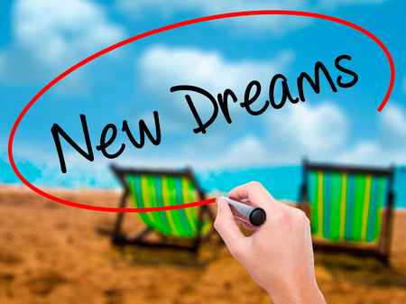 Man Hand writing New Dreams with black marker on visual screen. Isolated on sunbed on the beach. Business, technology, internet concept. Stock Photo