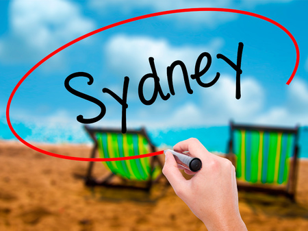 Man Hand writing Sydney  with black marker on visual screen. Isolated on sunbed on the beach. Business, technology, internet concept. Stock Photo Stock Photo