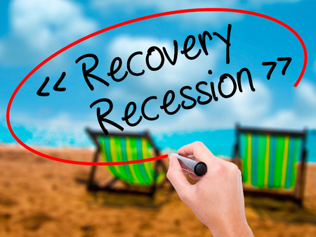 Man Hand writing  Recovery - Recession with black marker on visual screen. Isolated on sunbed on the beach. Business, technology, internet concept. Stock Photo Stock Photo