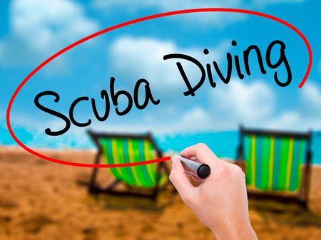 Man Hand writing Scuba Diving with black marker on visual screen. Isolated on sunbed on the beach. Business, technology, internet concept. Stock Photo Stock Photo