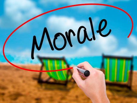 morale: Man Hand writing Morale with black marker on visual screen. Isolated on sunbed on the beach. Business, technology, internet concept. Stock Photo