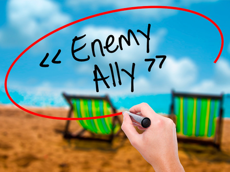 interdependence: Man Hand writing Enemy - Ally with black marker on visual screen. Isolated on sunbed on the beach. Business, technology, internet concept. Stock Photo