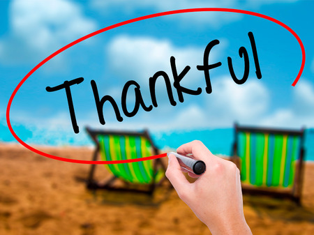 obliged: Man Hand writing Thankful  with black marker on visual screen. Isolated on sunbed on the beach. Business, technology, internet concept. Stock Photo