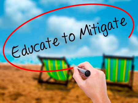 Man Hand writing Educate to Mitigate with black marker on visual screen. Isolated on sunbed on the beach. Business, technology, internet concept. Stock Photo