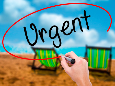 Man Hand writing Urgent  with black marker on visual screen. Isolated on sunbed on the beach. Business, technology, internet concept. Stock  Photo Stock Photo
