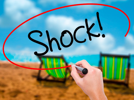 Man Hand writing Shock! with black marker on visual screen. Isolated on sunbed on the beach. Business, technology, internet concept. Stock Photo