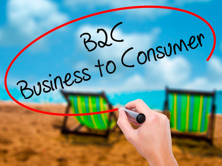Man Hand writing B2C Business to Consumer with black marker on visual screen. Isolated on sunbed on the beach. Business, technology, internet concept. Stock Photo
