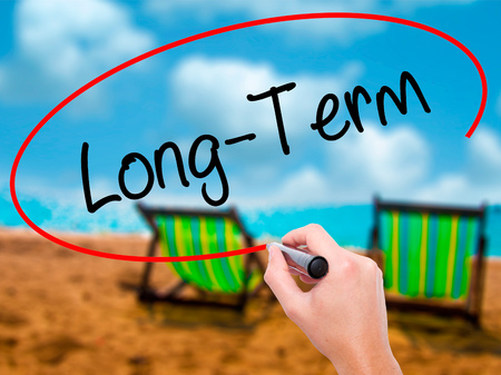 Man Hand writing Long-Term with black marker on visual screen. Isolated on sunbed on the beach. Business, technology, internet concept. Stock Photo