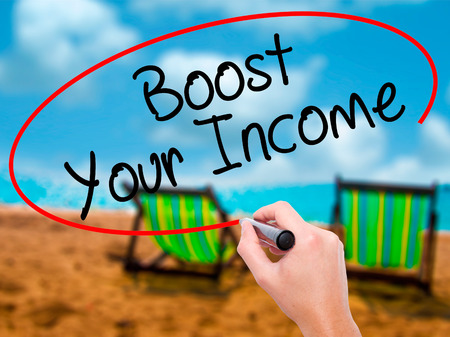 takings: Man Hand writing Boost Your Income with black marker on visual screen. Isolated on sunbed on the beach. Business, technology, internet concept. Stock Photo