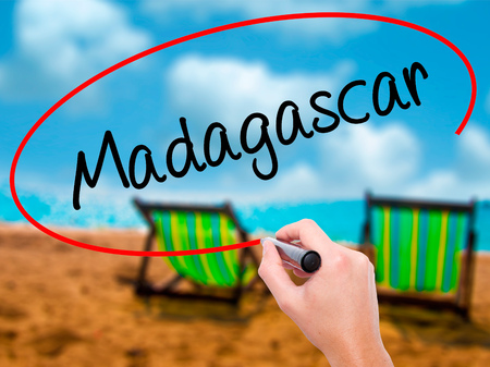 fort dauphin: Man Hand writing Madagascar with black marker on visual screen. Isolated on sunbed on the beach. Business, technology, internet concept. Stock Photo