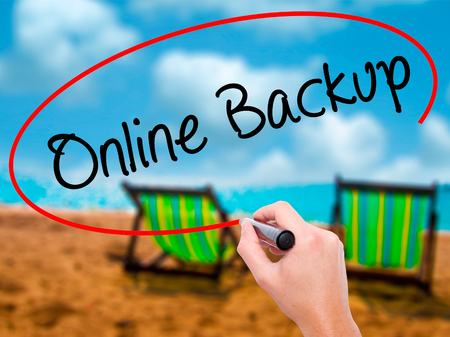 Man Hand writing Online Backup with black marker on visual screen. Isolated on sunbed on the beach. Business, technology, internet concept. Stock Photo