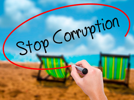 Man Hand writing Stop Corruption with black marker on visual screen. Isolated on sunbed on the beach. Business, technology, internet concept. Stock Photo