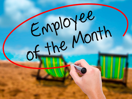 Man Hand writing Employee of the Month  with black marker on visual screen. Isolated on sunbed on the beach. Business, technology, internet concept. Stock Photo Stock Photo