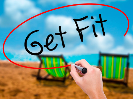 work less: Man Hand writing Get Fit  with black marker on visual screen. Isolated on sunbed on the beach. Business, technology, internet concept. Stock Photo