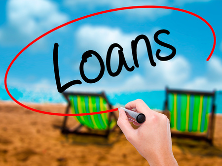 Man Hand writing Loans  with black marker on visual screen. Isolated on sunbed on the beach. Business, technology, internet concept. Stock Photo