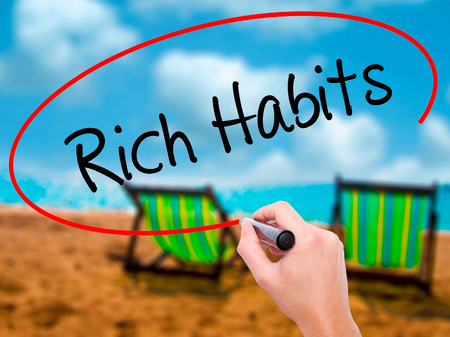 principles: Man Hand writing Rich Habits with black marker on visual screen. Isolated on sunbed on the beach. Business, technology, internet concept. Stock Photo