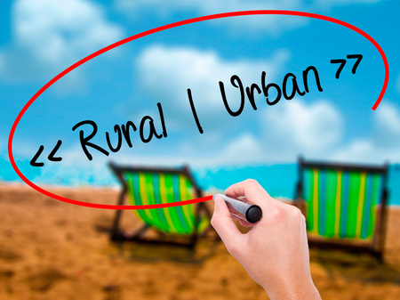 Man Hand writing Rural - Urban with black marker on visual screen. Isolated on sunbed on the beach. Business, technology, internet concept. Stock Photo Stock Photo