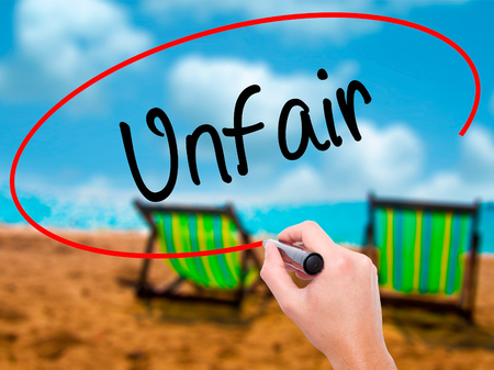 Man Hand writing Unfair with black marker on visual screen. Isolated on sunbed on the beach. Business, technology, internet concept. Stock Photo Stock Photo