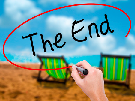 imminent: Man Hand writing The End with black marker on visual screen. Isolated on sunbed on the beach. Business, technology, internet concept. Stock Photo