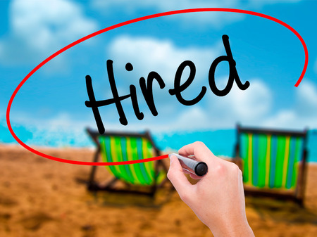employment agency: Man Hand writing Hired with black marker on visual screen. Isolated on sunbed on the beach. Business, technology, internet concept. Stock Photo
