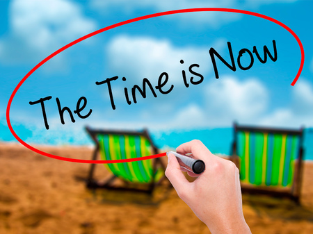 Man Hand writing The Time is Now with black marker on visual screen. Isolated on sunbed on the beach. Business, technology, internet concept. Stock Photo Stock Photo