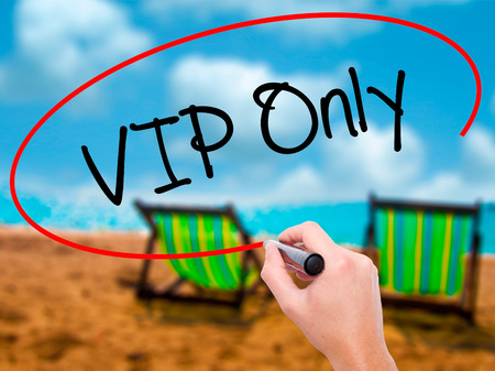 Man Hand writing VIP Only   with black marker on visual screen. Isolated on sunbed on the beach. Business, technology, internet concept. Stock Photo
