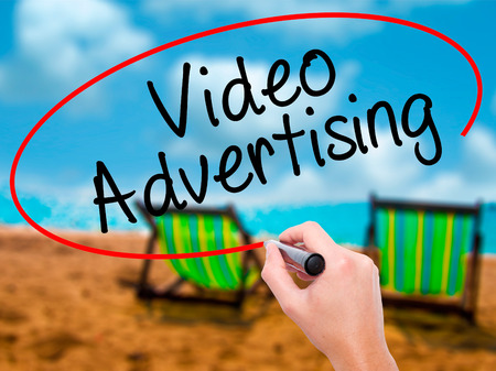 televisor: Man Hand writing Video Advertising with black marker on visual screen. Isolated on sunbed on the beach. Business, technology, internet concept. Stock Photo